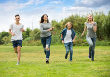 Teenagers running on green lawn in park Stock Images