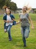 Teenagers running through green lawn in summer in park. Group of teenagers running through green lawn in summer in park stock photos