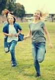 Teenagers running through green lawn in summer in park Royalty Free Stock Photography