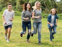 Teenagers running through green lawn in summer in park stock images