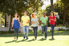 Teenagers Running Through Park Royalty Free Stock Photography