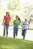 Teenagers Running Through Park Royalty Free Stock Image