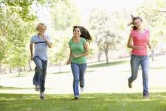 Teenagers Running Through Park Stock Photo