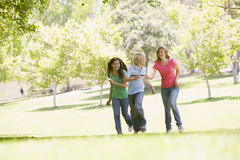 Teenagers Running Through Park Stock Photo
