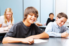 Teenagers in School. Class of teenagers in school, focus on suntanned boy in the front Stock Images