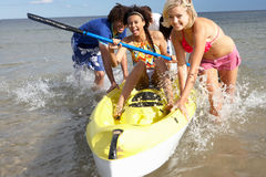 Teenagers in sea with canoe. Having fun stock images