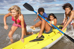 Teenagers in sea with canoe Stock Photography