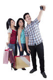 Teenagers with shopping bags taking pictures. Multi ethnic teenagers taking pictures in the studio while carrying shopping bags Stock Photography