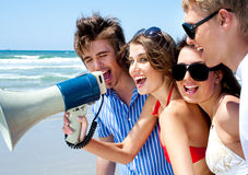 Teenagers shouting through megaphone Stock Images