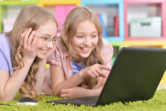 Teenagers sisters using laptop Royalty Free Stock Photo