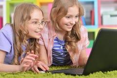 Teenagers sisters using laptop Stock Image
