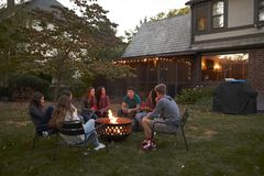Teenagers sit talking around a fire pit in a garden at dusk stock image