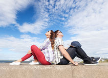 Teenagers sitting back to back. Summer holidays and teenage concept - teenagers sitting back to back and looking up in the sky Royalty Free Stock Image