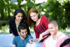Teenagers sitting on a bench and doing homework Royalty Free Stock Photography