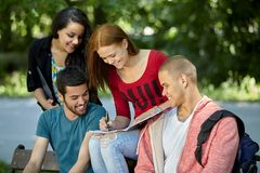 Teenagers sitting on a bench and doing homework Stock Photo