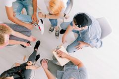 Teenagers sitting in circle. High angle of teenagers sitting in a circle during discussion with counselor about future career plans Stock Photos