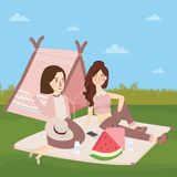 Teenagers sitting on the ground in front of tents, camping girls fun friendship Stock Photo