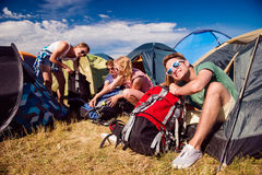 Teenagers sitting on the ground in front of tents Royalty Free Stock Image