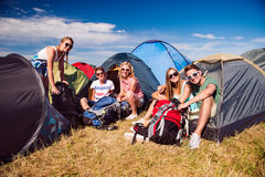 Teenagers sitting on the ground in front of tents Royalty Free Stock Photos
