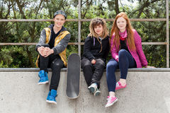Teenagers sitting on a halfpipe. Young friends sitting on a halfpipe in a skatepark Royalty Free Stock Photo