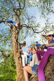 Teenagers sitting and holding mobiles on the tree Stock Photography