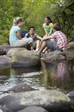 Teenagers Sitting On Stones By River In Forest Royalty Free Stock Photo