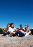 Teenagers sitting by a street Royalty Free Stock Images