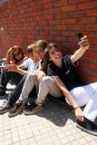 Teenagers sitting by a street Stock Images