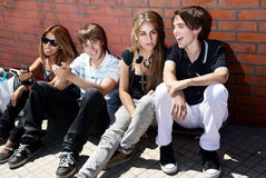 Teenagers sitting by a street Royalty Free Stock Photos