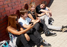 Teenagers sitting by a street Stock Photos
