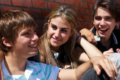 Teenagers sitting by a street Royalty Free Stock Image
