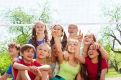 Teenagers sitting under volleyball net pointing Stock Images