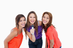Teenagers smiling while singing a karaoke Stock Image