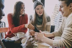 Teenagers Socialising In A Winter Cafe. Teenagers socialising in a cafe in winter Royalty Free Stock Image
