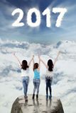 Teenagers stand on rock with 2017 at sky Stock Images