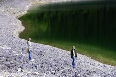 Teenagers stand on stones on the bank of the lake, which reflects the forest, hiking in the forest. Summer vacation stock image