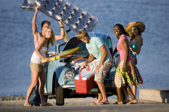 Teenagers (17-19) standing beside car near water, carrying cool box and inflatable, smiling Royalty Free Stock Image