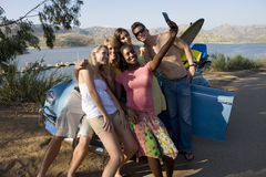 Teenagers (17-19) standing beside car with surfboard, girl taking photograph with camera phone Stock Photography