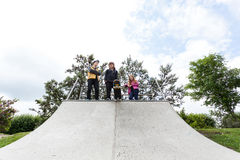 Teenagers standing on a halfpipe. Three friends standing at the top of a halfpipe Stock Photos