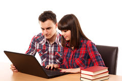 Teenagers studying together with a laptop. Couple of teenagers studying, doing homework on a laptop Stock Photography