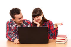 Teenagers studying together with a laptop. Couple of teenagers studying, doing homework on a laptop Royalty Free Stock Photo