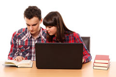 Teenagers studying together with a laptop. Couple of teenagers studying, doing homework on a laptop Stock Image