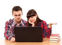 Teenagers studying together with a laptop. Couple of teenagers studying, doing homework on a laptop Royalty Free Stock Photos
