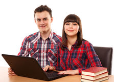 Teenagers studying together with a laptop. Couple of teenagers studying, doing homework on a laptop Royalty Free Stock Images