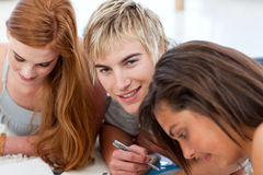 Teenagers studying together lying on the floor Stock Photos