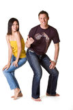 Teenagers style. Caucasian guy pointing to Asian girl with him thumb while their hips touching each other Stock Image