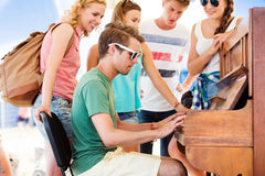 Teenagers at summer music festival, boy plays the piano. Group of teenage boys and girls at summer music festival, handsome young men plays the piano. Sunny day Royalty Free Stock Photos
