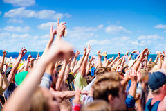 Teenagers at summer music festival clapping and singing. Teenagers at summer music festival under the stage in a crowd enjoying themselves, clapping and singing royalty free stock photography