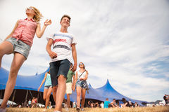 Teenagers at summer music festival in front of big blue tent. Group of teenage boys and girls at summer music festival walking in front of big blue tent, sunny Royalty Free Stock Photo