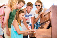 Teenagers at summer music festival, girl plays the piano. Group of teenage boys and girls at summer music festival, beautiful young women plays the piano. Sunny Stock Photo